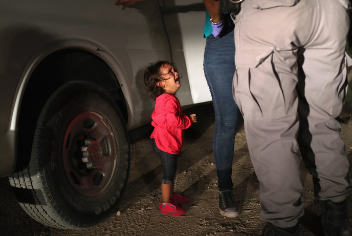 Honduran cries as her mother is searched and detained