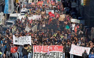 """Demonstration against the French government's pensions reform plans in Marseille, France, December 10, 2019. The slogan reads """"work, shop and shut up,"""" referring to the government's attitude toward workers."""