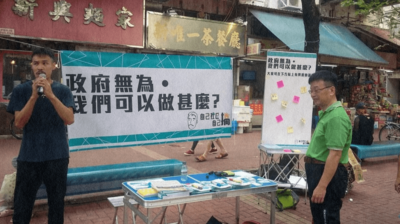 Kuen (left) at a Community Self-Organizing booth with Leung Po-lung (right).
