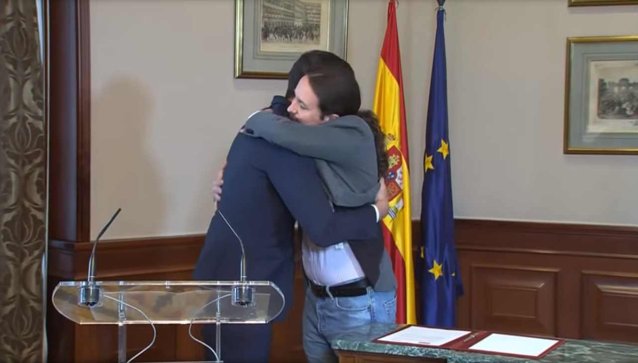 Pedro Sánchez and Pablo Iglesias hug at their November 12, 2019 announcement of their agreement to form a coalition government. The formation of the coalition government prompted Anticapitalistas to leave Podemos.