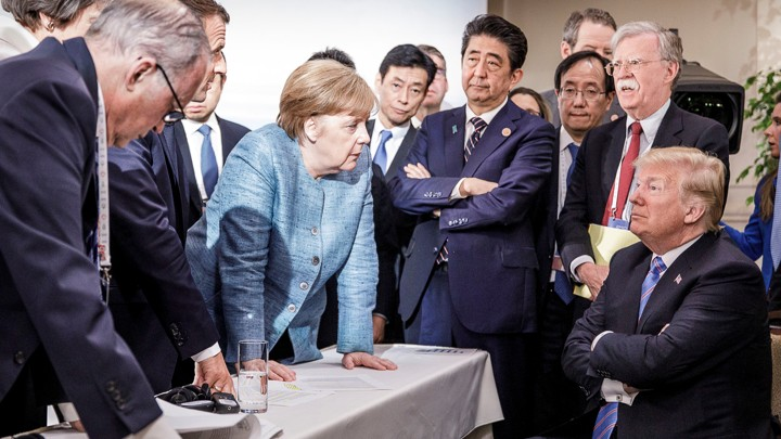 German Chancellor Angela Merkel speaks to U.S. President Donald Trump during the second day of the G7 meeting in Quebec, June 9, 2018